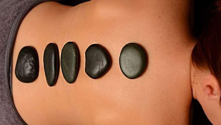 Masaje con piedras volcánicas en camilla de madera